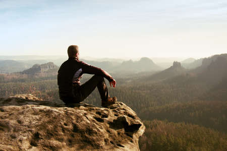Young man in black sportswear is sitting on cliff's edge and looking to misty valley bellow
