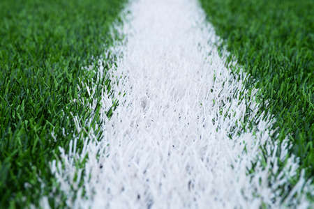 White line marks painted on artificial green turf background. Winter football playground with plastic grass.
