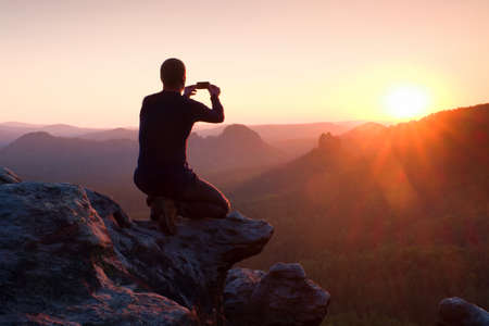 Young man in black sportswear is sitting on cliff's edge and taking photos by smart phone Archivio Fotografico