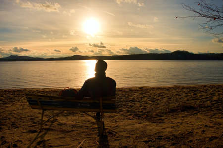 Alone Young Man In Silhouette Sitting In The Sun. Tourist take a rest on the wooden bench at autumn lake.