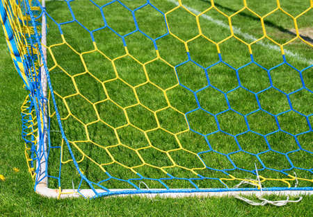 Hang bended blue yellow soccer nets, soccer football net. Grass on football playground in the background