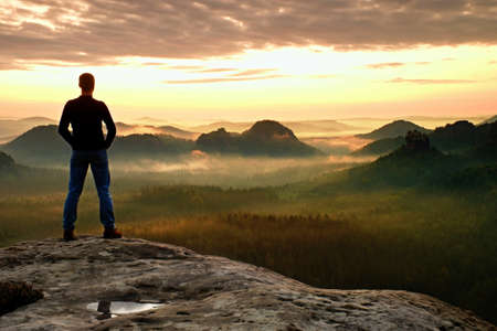 Hiker is standing on the peak of sandstone rock in rock empires park and watching over the misty and foggy morning valley to Sun. Beautiful moment the miracle of nature