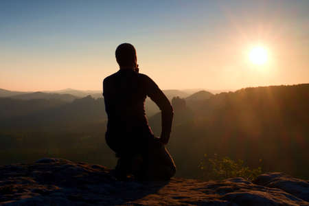 Sportsmann hiker in black sportswear sit on mountain top and take a rest with watching down to morning valley.