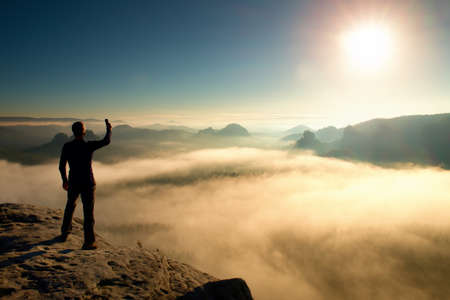 Hiker is taking photo by smart phone on cliff of mountain at sunrise.