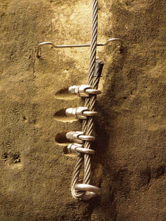 Climbers way. Iron twisted rope fixed in block by screws snap hooks. The rope end anchored into sandstone rock. Standard-Bild