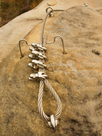 Iron twisted rope fixed in block by screws snap hooks. Detail of rope end anchored into rock