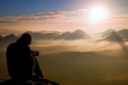 Photographer silhouette above a clouds sea, misty mountains