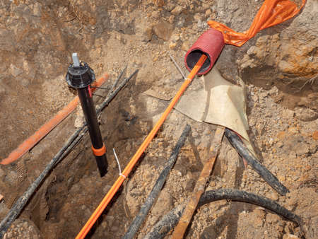 Safety tube with optic fiber cables. Bulding site with trench for underground telephone optical lines
