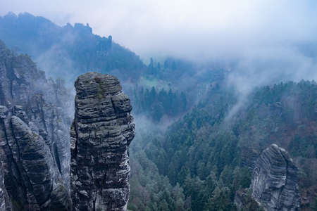 Dark blue highland scenery within misty weather aerial view. Rocky tower. Soft Sunlight Eco Friendly Environment Concept Drone Flight