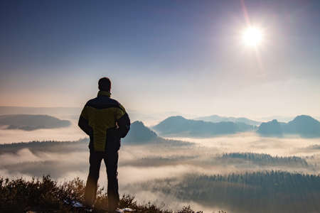 Hiking Man Silhouette enjoying amazing colorful sunset mountains. Fantastic panorama of misty and foggy layered mountains with dramatic clouds.
