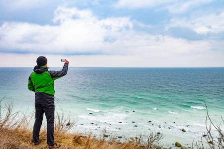 Traveler man with phone camera takes photo of windy sea on coast.
