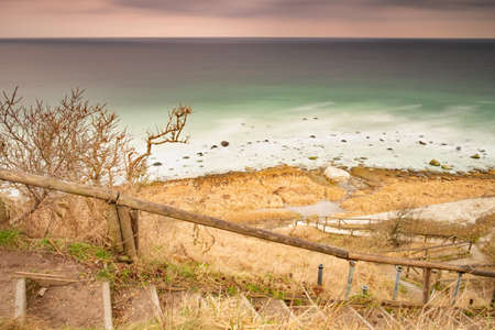 Downstairs path to the beach of Cape Arkona chalk cliff at Baltic sea. Autumn weather and wavy sea in long exposure