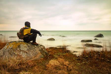 Tourist sit in boulder at north peak of Ruegen island in winter time. Strong wind creat milky foam waves at stony coast. Stock fotó