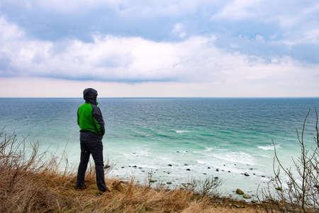 Man at coast. Boulders and white rocks at the coast of cape arkona Stock fotó