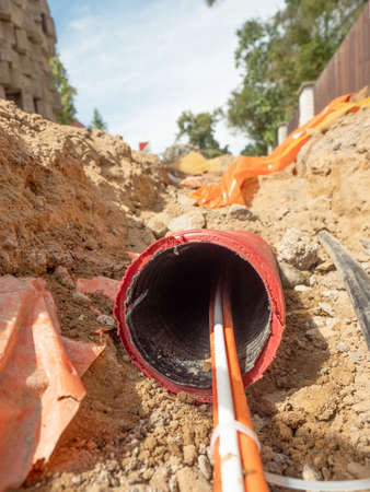 Data fiber optic cables in ribbed pipe under road. Wire in HDPE and protectivep tube. Building of lines of metallic and optic cables,