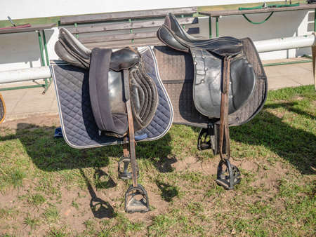 Comfortable saddles laying on fence in warm sunlight. Stable background with mooring bar. Stock Photo