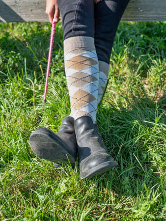 Crossed legs wear riding paddock boots and long knee socks. Horse rider hold wisp while sit in paddock of horse riding club. Stockfoto