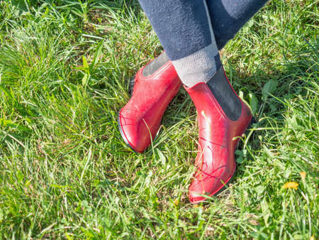 Young girl in red paddock boots with long tighs sitting in grass and waiting for her horse and lesson. Stockfoto