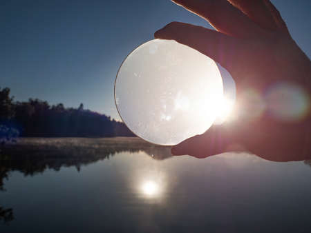 Hand hold glass lens or ball uniquely reflects summer lake scene with sunset.