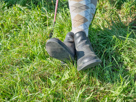 Young girl in paddock boots with long tighs sitting in grass and waiting for her horse and lesson.