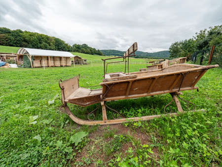 Old wooden sledge for snow wait in grass of meadow. Horse farm wait for winter vacation Standard-Bild
