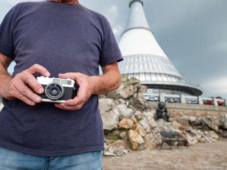 Old man visit Jested hill and taking photos by classic vintage camera.