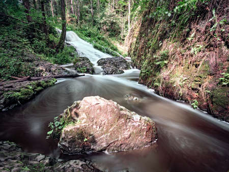 Fallen rocks and rapids in forest. Curved mountain stream flowing down on basalt rock.