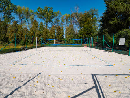 Closed beach volleyball court in fall season. Autumn weather and fallen leaves on white playground sand.