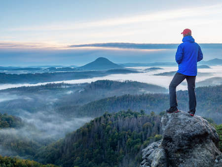 Man on the mountain peak looking at mountain valley with heavy mist at colorful sunset in early autumn. Landscape with traveler, foggy hills 스톡 콘텐츠
