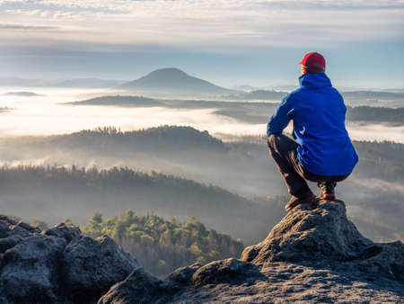 Nature adventure. Hiker sit on the rock and watch over the misty morning valley to rising sun at horizon.