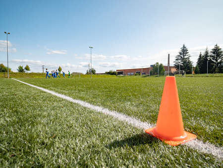 Orange border cone. Soccer training court line and cone equipment on green field for football sports.