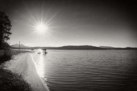 Abandoned old rusty paddle boat stuck on sand of beach. Wavy water level, island on horizon.