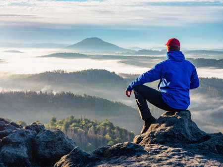 Man on the peak of rock. Man sit with hand on knee with beautiful sunrise landscape. Hiker is watching into colorful mist and fog in forest valley.