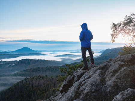 Hiking in sunrise. Man hiker wear hood and blue windcheater stay alone in sunset at mountain edge. Healthy and sport people lifestyle