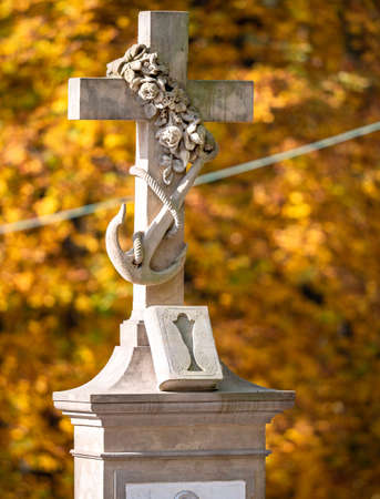 The flower rope and sea anchor. Anchor with a cross as Christian symbol of hope. 24th of October 2020. Hronov, Czechia. Orange autumnal chestnut tree in background. Stok Fotoğraf