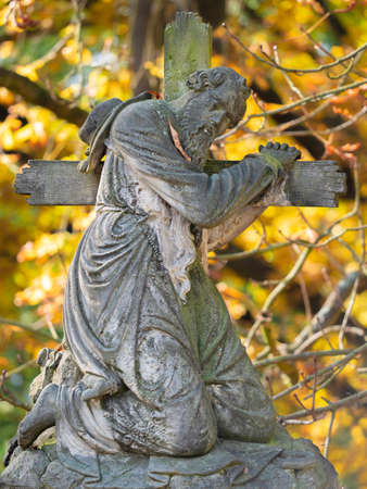 The man hold wooden cross, graveyard statue on tombstone. 24th of October 2020. Hronov, Czechia. Heloween walk in old town graveyard