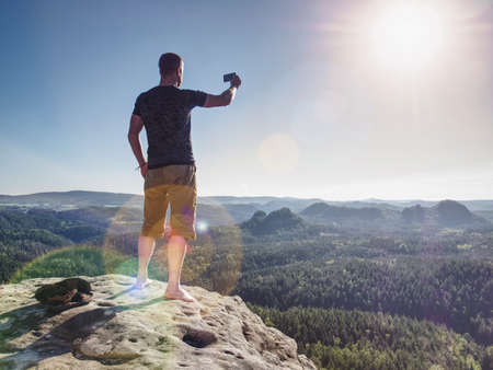 Trendy, fit and strong barefoot man athlete in running shorts and light stripped t-shirt makes mobile smartphone photo or selfie. Strong sun flares.