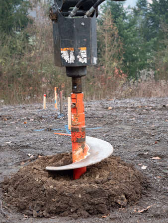 Turning drill auger with ground and dirt. The auger, industrial ground drilling rig making a hole.