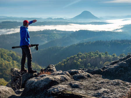 Photographer in silhouette carrying camera on tripod. Natural photographer hold camera with tripod and watch to the misty mountain valley