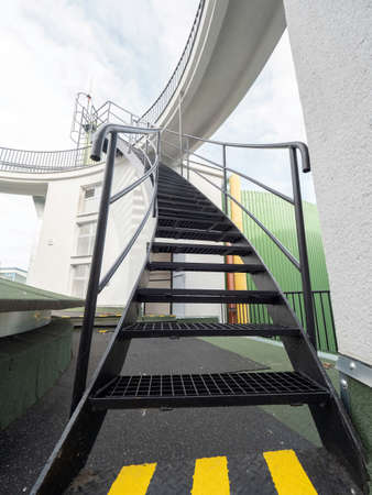 Outdoor stairs of an escape exit in a factory. Yellow markings on the floor show the shortest way to safety.