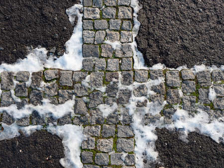 Cobblestones in pavement covered with snow. The mosaic on the square.