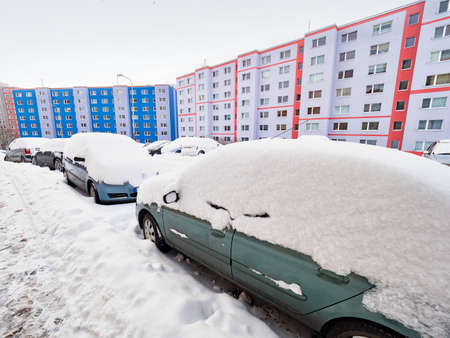 Abandoned cars buried under a snowdrift in winter in the parking lot. Colorful flat houses in background