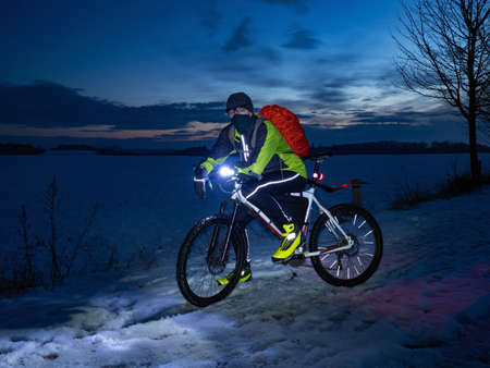 Guy cyclist sits on a MTB during a night ride. City park and light snowfall in the fog.