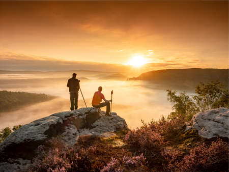 Two matured photographers at the hilltop with his tripod and camera search of good object to make a final photography session at sunset time. Stock fotó