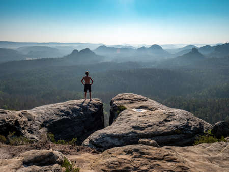 Tall shirtless male sports figure on the edge of a rock enjoys the view of the morning landscape.