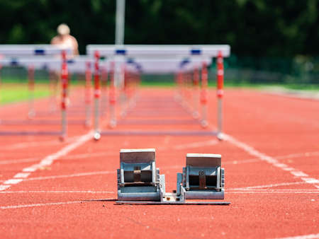 Obstacle course training. Athletics Starting Blocks and red running tracks in a stadium