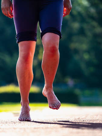 Solid bare feet of a hard training woman. A woman runs along the soft surface of a running track in short leggings. Imagens