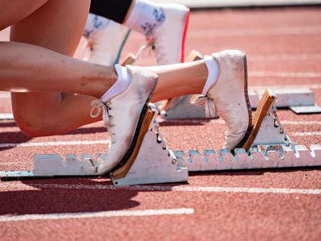 Side view of female feet on starting block ready for a sprint start. Naked female legs in light running shoes.