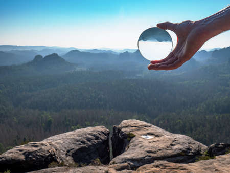 Crystal glass ball in a man's hand. The morning misty hilly landscape is reflected in the lens.