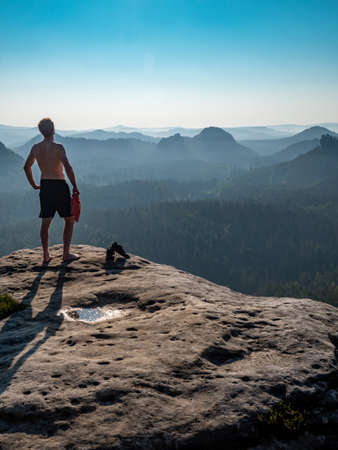 Shirtless man with a sports figure on the edge of a rock enjoys the view of the morning landscape.